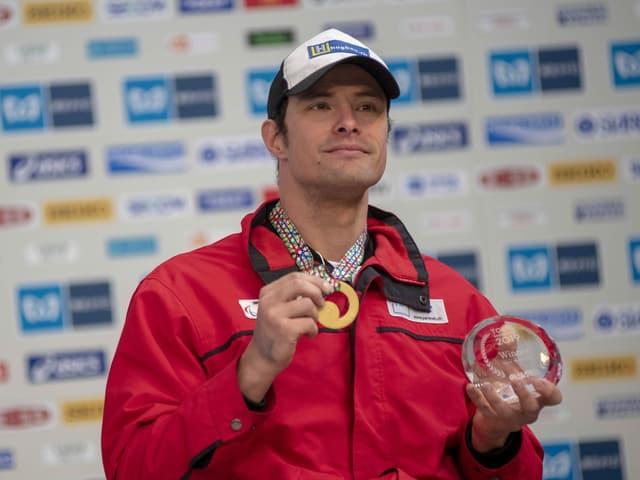 Marcel Hug posiert mit einer Goldmedaille um den Hals.