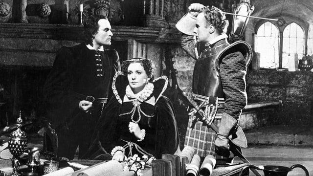 Eine Szene aus einem alten Film: Eine Königin in prunkvollem Gewand sitzt an einem Tisch, links und rechts von ihr stehen zwei Männer und schauen sich in die Augen. Die Königin schaut starr geradeaus.