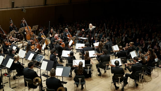 Eine blonde langhaarige Dirigentin mit Orchester bei einem Live-Auftritt.