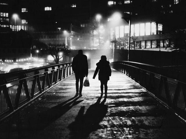 Ein Paar auf einer Brücke in der Nacht.