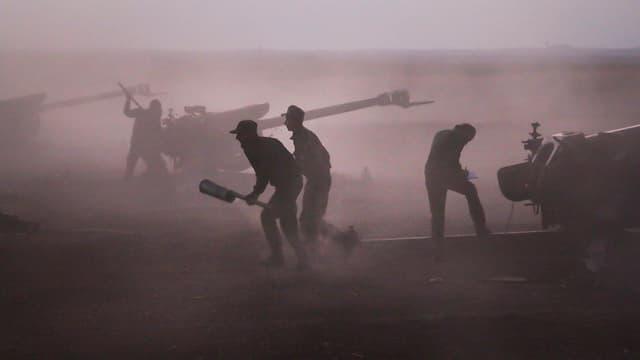 Syrische Soldaten bei einer Artilleriestellung.