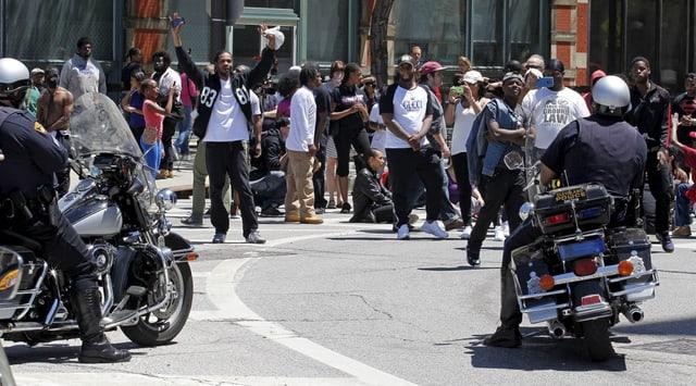 Protestierende werden von zwei Polizisten auf Motorrädern beobachtet.