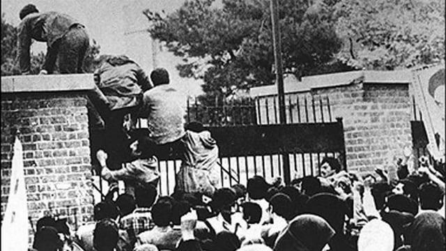 Leute klettern über die Botschaftsmauer in Teheran. Schwarzweiss-Foto.