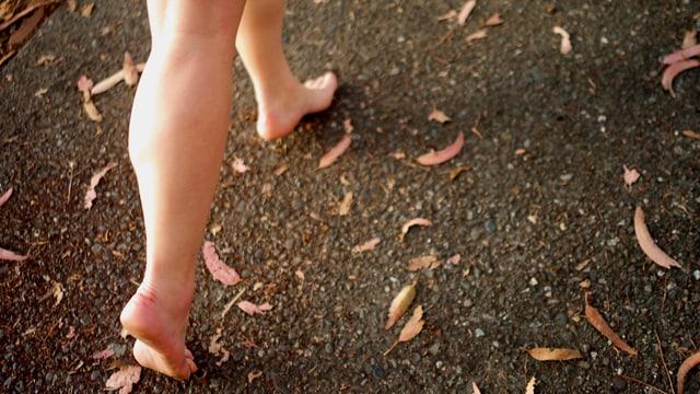 Ein Mädchen rennt barfuss auf dem Asphalt