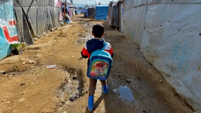 Ein Junge mit Rucksack geht zwischen Zelten hindurch.
