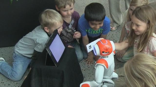 Kinder sitzen um einen Roboter