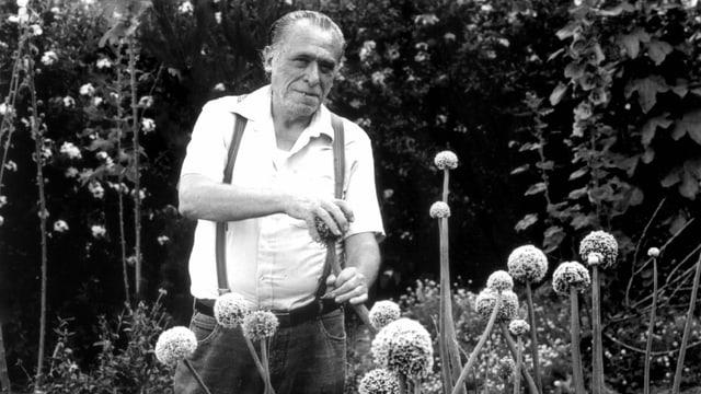 eine schwarz-weiss Aufnahme eines Mannes im Blumengarten