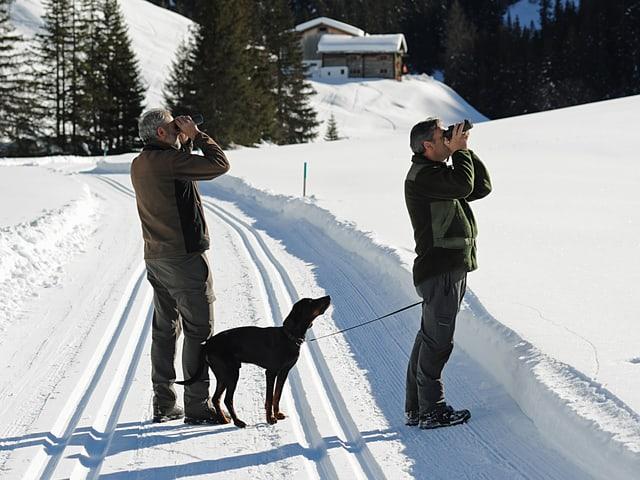 Zwei Wildhüter mit Fernrohren, ein Hund.