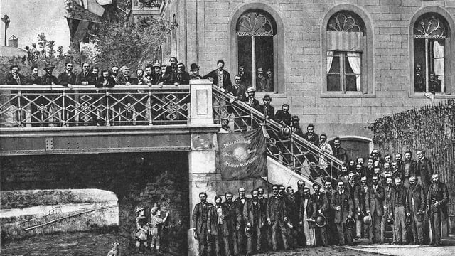 Viele Männer stehen vor einer Treppe vor einem grossen Haus in der Stadt.