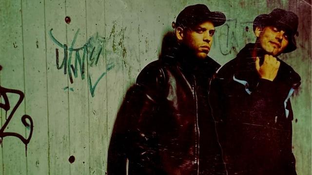 Zwei junge Männer lhenen an einer Betonwand.