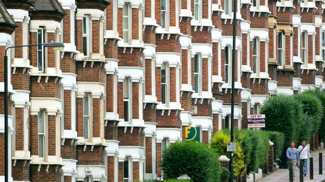Strassenzug mit aneinandergebauten Backsteinhäuser in London.