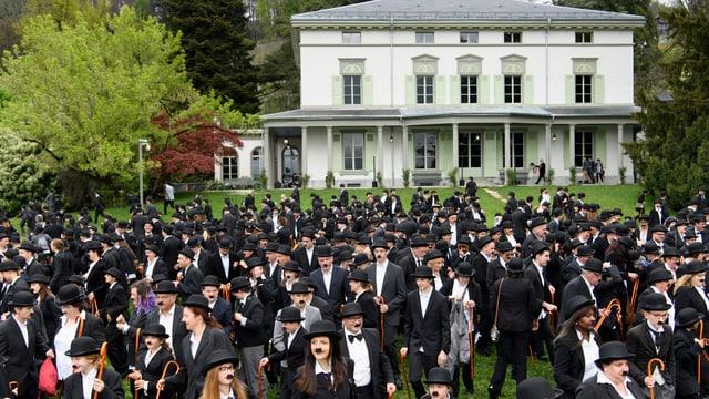 Hunderte als Charly Chaplin verkleidete Menschen versammeln sich in einem Garten