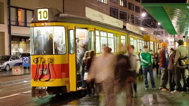Gelbes 10er Tram und Leute, die ein- und aussteigen