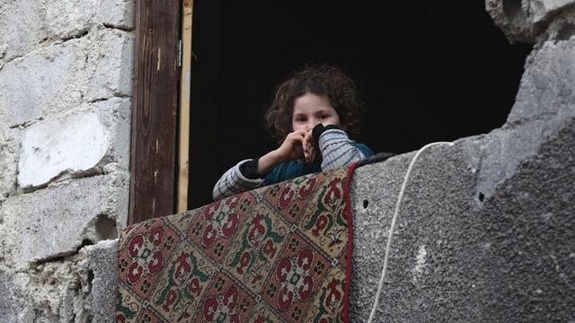 Mädchen schaut aus grossem Fenster. Das Haus hat Schäden vom Krieg.