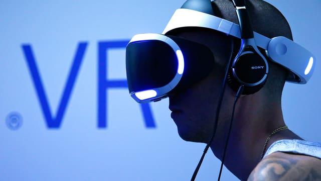 Junger Mann mit Tattoos trägt eine Virtual-Reality-Brille, eingetaucht in blaues Licht.