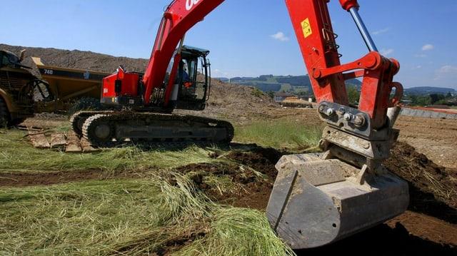 Ein Bagger gräbt ein Loch in eine Wiese.