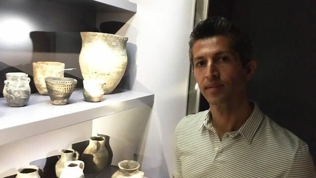 Hemen Saidpur vor einer Vitrine mit römischen Tonkrügen und Vasen