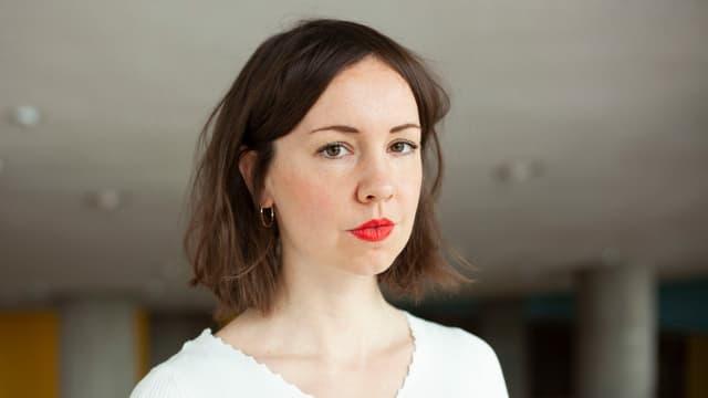 Frau mit braunen Haaren und rotem Lippenstift schaut in die Kamera