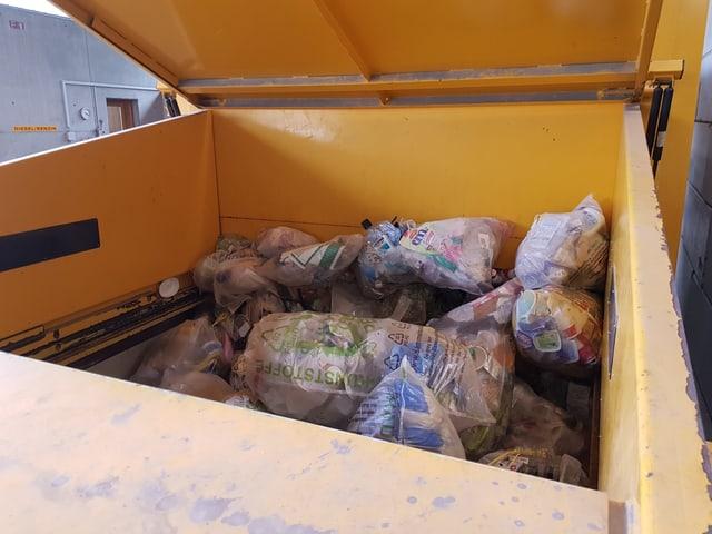 Satgs emplenids cun  plastic en il container da pressa.