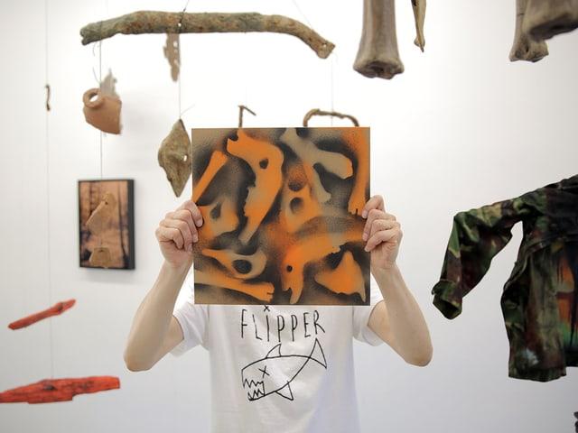 Eine Person hält eine Grafik vor ihr Gesicht. Im Hintergrund hängen verschiedene Objekte.