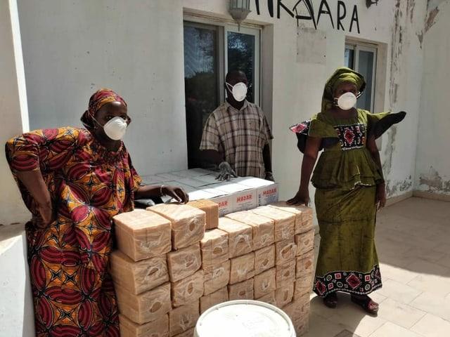 Zwei Frauen und ein Mann lehnen auf einem Stapel voller Seife.