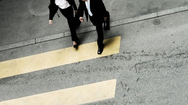 Frau und Mann gehen in Gleichschritt über einen Fussgängerstreifen.