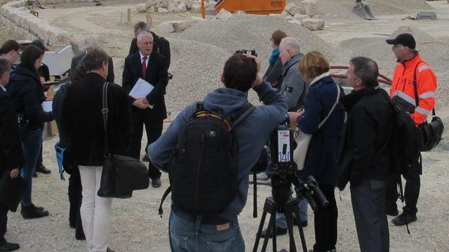 OB Wolfgang Dietz spricht auf einer Baustelle zu einer Gruppe von Journalisten