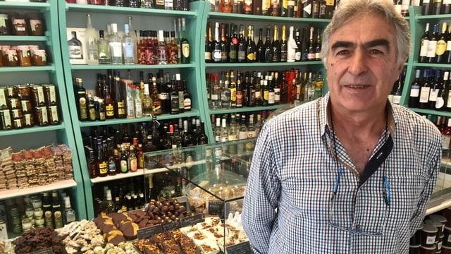 Mann in einem Laden vor Süssigkeiten und Getränken.