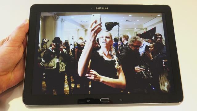Frau in Menschenmenge macht Selfie
