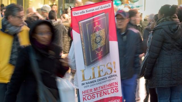 Menschen in Fussgängerzone, in der Mitte ein Plakat einer Koran-Verteilaktion.