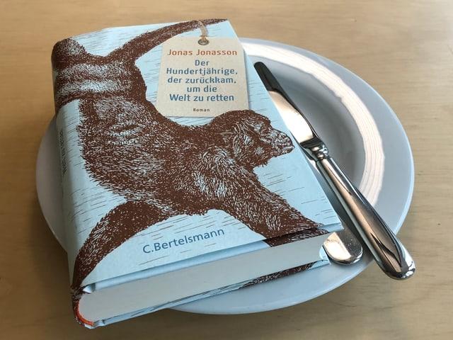 «Der Hundertjährige, der zurückkam, um die Welt zu retten» liegt auf einem weissen Teller. Messer und Gabel seitlich neben das Buch auf den Teller gelegt.