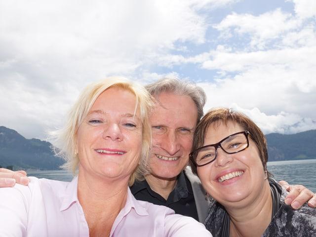 Schnappschuss mit drei lachenden Menschen.