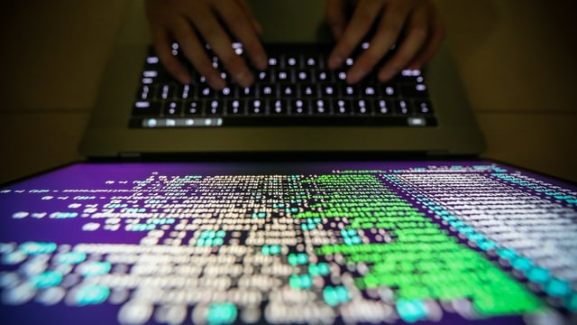 Hände und Tastatur vo einem Computerbildschirm.