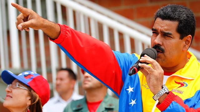 Maduro spricht zu seinen Anhängern. Er trägt eine Trainingsjacke in den Farben der venzolanischen Flagge.