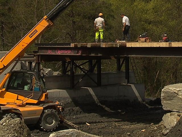 Arbeiter erstellen im Rüfengebiet eine Notbrücke.