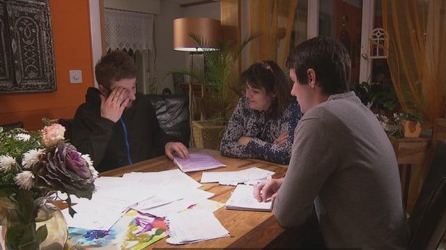 Mutter mit zwei Söhnen sitzen am Tisch und studieren Dokumente.
