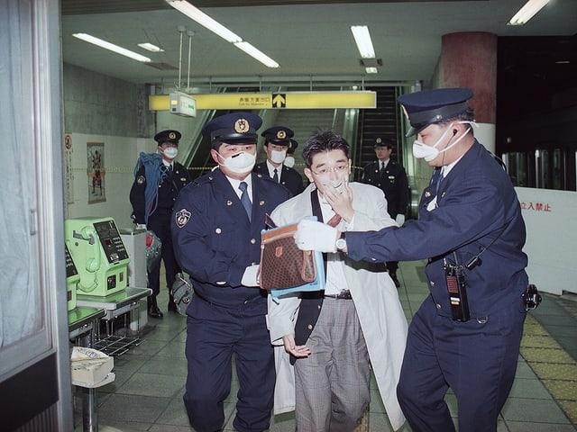 Polizisten mit Atemmasken führen einen Mann aus der U-Bahn.