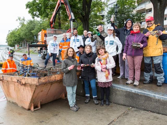 Gruppe von Helferionnen und Helfern posiert neben einer Abfalltonne.