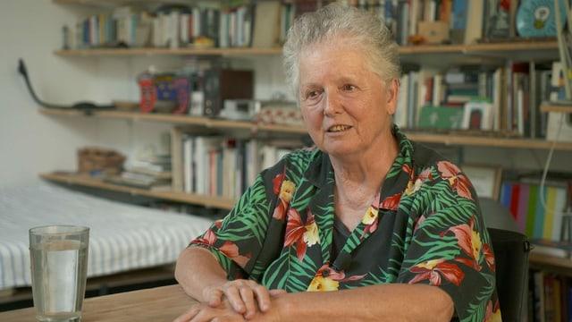Künstlerin Miriam Cahn sitzt bei einem Glas Wasser vor einer Bücherwand.