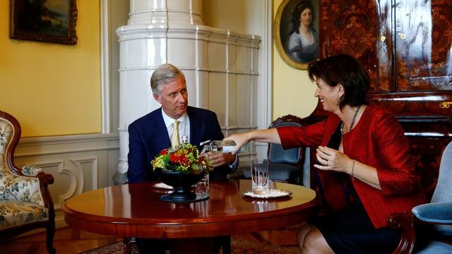 Die Bundespräsidentin bietet dem König ein Glas Wasser an.