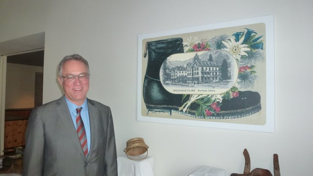 Olaf Reinhardt, il directur ad interim dal hotel Adula, davant in maletg che mussa ina veglia charta da posta dal hotel.