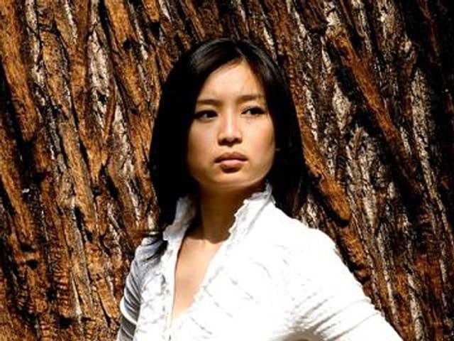 Mei Yi Foo steht vor einem Baum.