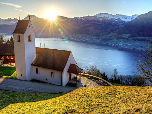 Kapelle hoch über dem See und dahinter Sonnenaufgang über den Alpen