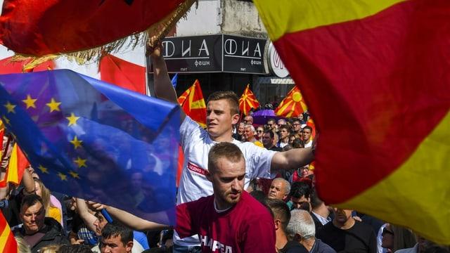 Männer mit Fahnen von EU und Nordmazedonien.