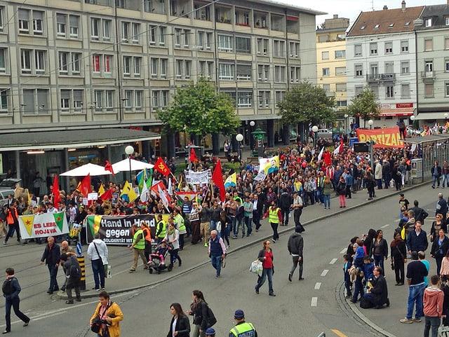 Demonstranten mit Fahnen ziehen durch Basel