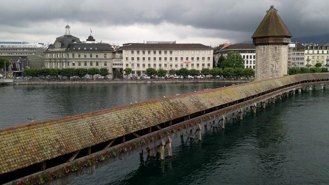 Ein lange Holzbrücke und alte Gebäude an einem Seeufer bei Regenwetter.