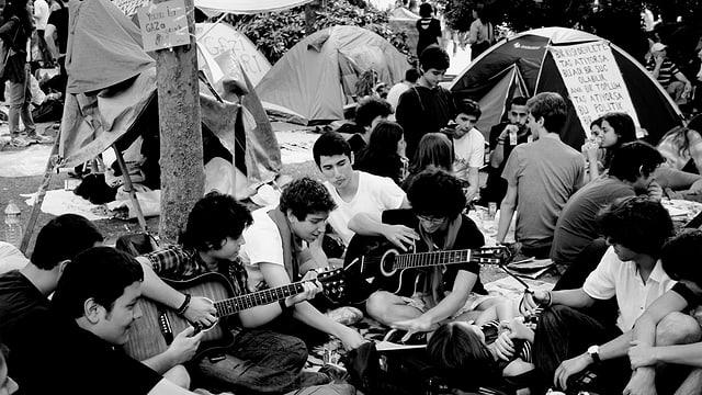 Junge Menschen sitzen auf dem Taksimplatz und spielen Gitarre.