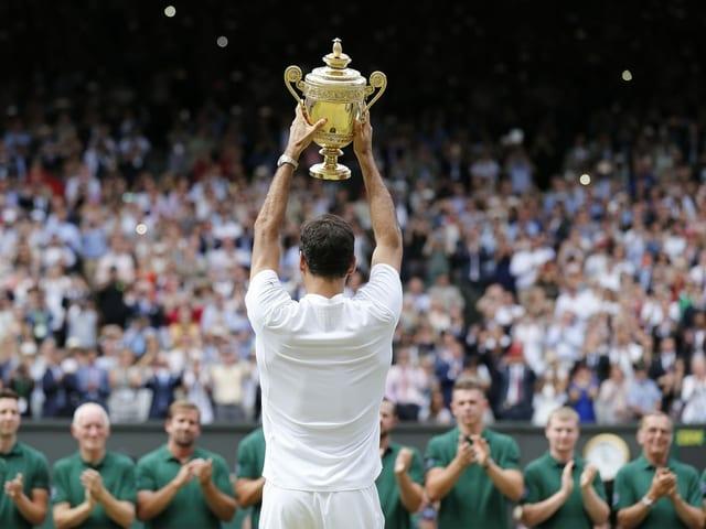 Roger Federer von hinten, wie er dem Publikum die Trophäe präsentiert.