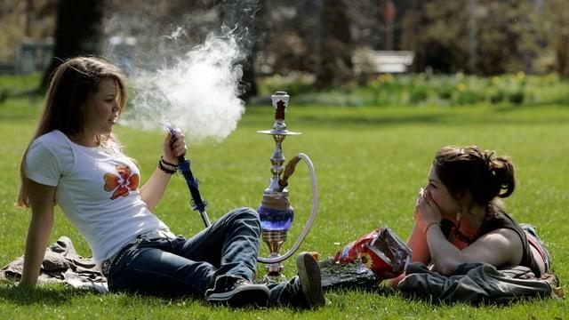 Zwei junge Frauen rauchen auf einer Wiese eine Wasserpfeife.