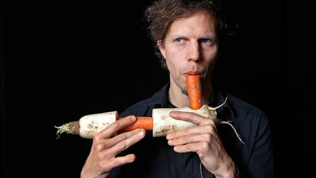 Ein Mann bläst durch eine Karotte, die wiederum an einem Rettich befestigt ist.